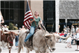 Woman riding a longhorn and carrying an American flag during a parade