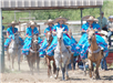 Women in blue dresses and sombrous on horses during a Rodeo