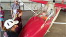Boy inside glider with kids looking on